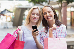 Happy women friends smiling at camera with shopping bags Royalty Free Stock Images