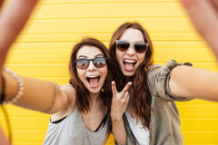 Happy women friends standing over yellow wall Royalty Free Stock Photography