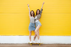 Happy women friends standing over yellow wall. Picture of two young happy women friends standing over yellow wall. Looking at camera Stock Image