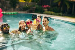 Group of friends catching memories from pool party. Happy women with friends taking selfie in swimming pool. Group of men and women enjoying pool party and Stock Photo