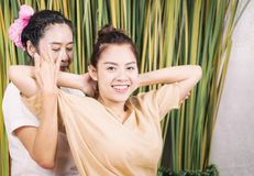 Happy woman is getting thai massage stretching. Happy women is getting thai massage stretching position royalty free stock image