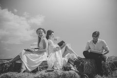 Happy women or girls reading books on bench. Man or macho typing on vintage typewriter on hay Royalty Free Stock Images
