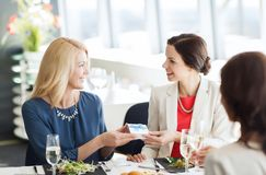 Happy women giving birthday present at restaurant Royalty Free Stock Image