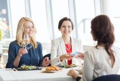 Happy women giving birthday present at restaurant Royalty Free Stock Photo