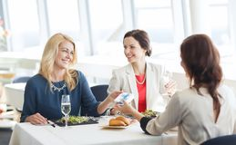 Happy women giving birthday present at restaurant Stock Photo