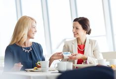 Happy women giving birthday present at restaurant Stock Images
