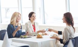 Happy women giving birthday present at restaurant Stock Photography
