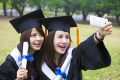 Happy women in graduation gowns taking picture with cell pho. Two happy women in graduation gowns taking picture with cell phone Royalty Free Stock Images
