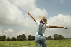 Asia women on meadow. Happy women with hat standing extend the arms on meadow under blue sky Stock Image
