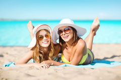 Happy women in hats sunbathing on beach. Summer holidays, vacation, travel and people concept - smiling young women in hats and lying over exotic tropical beach Stock Photos