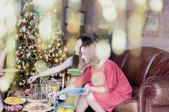 Happy women having some snacks with champagne while celebrating Christmas. Happy women having some snacks with champagne at the table while celebrating at Stock Photos