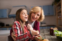 Grandmother and cute granddaughter cooking salad. Happy women and her daughter making fun in kitchen. Cooking together Royalty Free Stock Photography