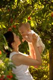 Happy woman holding in arm a baby in a garden. Happy family. royalty free stock photography
