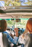 Happy women holding hands inside of car Royalty Free Stock Photos