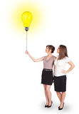 Happy women holding a light bulb balloon Stock Photography