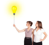 Happy women holding a light bulb balloon Stock Images