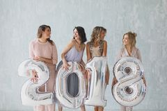 Beautiful young women holding silver 2018 sign balloons and smiling at camera. New Year party Royalty Free Stock Photo