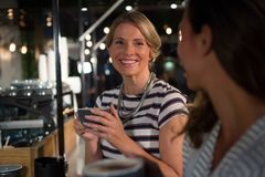 Happy woman interacting while having coffee. Happy women interacting while having coffee in restaurant Stock Photo