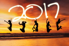 Happy women jumping on beach. Silhouette of happy women jumping on beach with number 2017 on the sky Royalty Free Stock Image