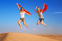 Happy women jumping in the desert Stock Photos