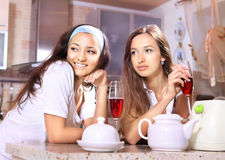 Happy women on kitchen. Happy women with glasses of red wine talk about on kitchen royalty free stock photography