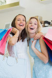 Happy women laughing together and holding shopping bags Stock Photos
