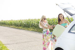 Happy women loading luggage in car trunk against clear sky Stock Photography