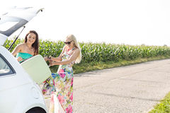Happy women loading luggage in car trunk against clear sky Royalty Free Stock Image