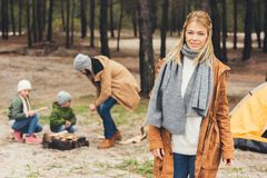 Happy woman looking at camera while her husband and kids making campfire. Happy women looking at camera while her husband and kids making campfire on nature Stock Image