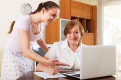Happy women looking financial documents in laptop. At table in home interior Royalty Free Stock Photo