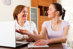 Happy women looking financial documents in laptop Royalty Free Stock Image