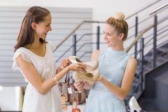 Happy women looking at heel shoes Stock Image