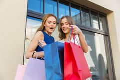 Happy women looking into shopping bags outdoors Stock Photo
