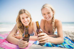 Happy women lying on the beach with beer bottle Royalty Free Stock Photography