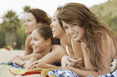 Happy Women Lying Down On Beach royalty free stock photo