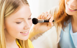 Happy women with makeup brush applying blush Royalty Free Stock Photos