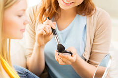 Happy women with makeup brush applying blush Royalty Free Stock Photo