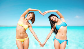 Happy women making heart shape on summer beach Stock Image