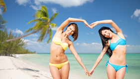 Happy women making heart shape on summer beach. Summer holidays, travel, people, love and vacation concept - happy young women in bikinis making heart shape with Royalty Free Stock Photo