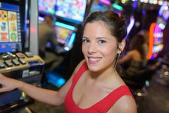 Happy woman next to slot machine. Happy women next to a slot machine Stock Images