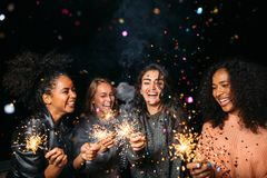 Happy women at night. Laughing friends with sparklers under confetti Royalty Free Stock Image