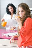 Happy women with orange juice at domestic kitchen Royalty Free Stock Photos