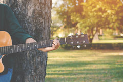 Happy women playing guitar. In nature relax time on holiday Stock Image