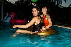 Friends having fun during evening pool party. Happy women in the pool with inflatable ring. Female friends having fun during evening pool party Stock Images