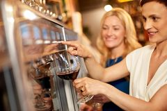 Free Happy Women Pouring Wine From Dispenser At Bar Royalty Free Stock Photos - 134103638