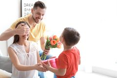 Happy woman receiving gifts from her husband. Happy women receiving gifts from her husband and son at home. Mother`s day celebration stock images