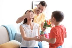 Happy woman receiving gifts from her husband and son. Happy women receiving gifts from her husband and son at home. Mother`s day celebration royalty free stock photos