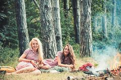 Happy women relax on green grass. Beauty girls with long hair at bonfire. Fashion women smile in retro dresses in forest. Summer vacation concept. Camping stock images