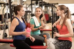 Happy women resting after workout in fitness gym Royalty Free Stock Image