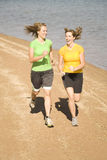 Happy women running on beach. Two happy women running together on the beach Stock Images